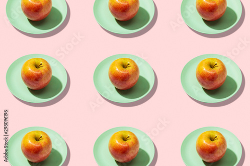 Fresh apple in plate on pink background. Vibrant colorful pattern - 298096196
