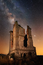 Dilapidated Old Brick Tower On Deserted Field Against Majestic Starry Sky