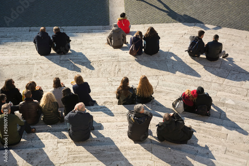 obraz PCV Crowd of people sitting on city stairs back behind top view. Concept of rest and meet in the city