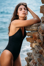 Side View Of Attractive Pensive Woman In Black Swimwear Relaxing On Seashore Leaning By Stone Wall And Looking At Camera