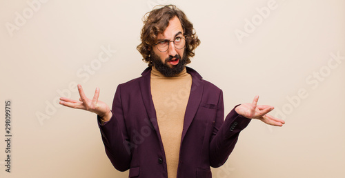 Fototapeta young bearded crazy man shrugging with a dumb, crazy, confused, puzzled expressi