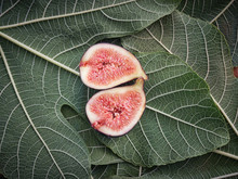 From Above Half Pieces Of Fig Over Wooden Table With Green Leaves