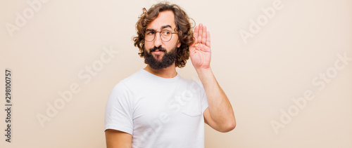 Fotografía young bearded crazy man looking serious and curious, listening, trying to hear a