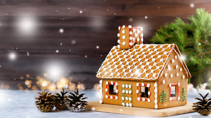 Sweet decorated gingerbread house closeup with pine cones decorations, fir tree branches, bokeh and snowfall. Christmas card with dark background, copy space