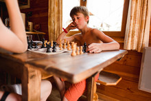 Two Kids Playing A Game Of Chess In The Summer In A Chalet