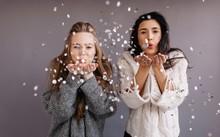 Two Girlfriends Blowing Confetti