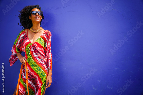 Photo  summer fashion, girl dressed with colorful clothes on blue background