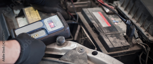 Car mechanic checking and testing automotive accumulator with battery tester Wallpaper Mural
