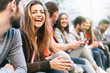 canvas print picture - Group of trendy young people chatting together sitting on a bench outdoors. Students having fun together. Focus on a blonde girl smiling with open mouth