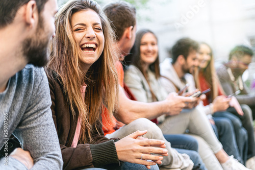 Group of trendy young people chatting together sitting on a bench outdoors. Students having fun together. Focus on a blonde girl smiling with open mouth