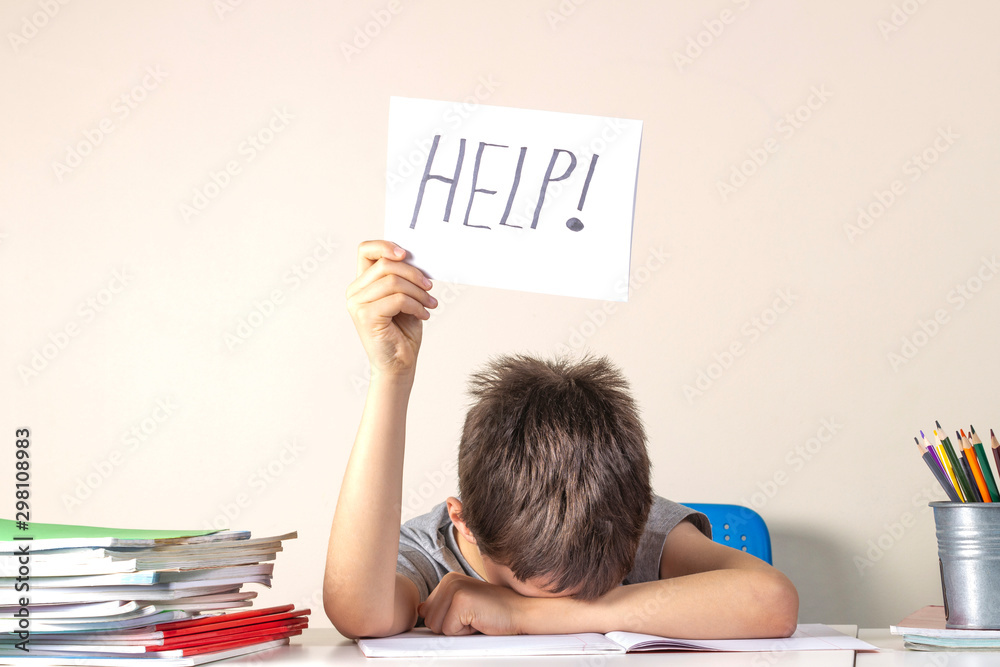 Fototapeta Sad tired frustrated boy sitting at the table with many books and holding paper with word Help. Learning difficulties, education concept.