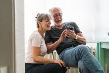 Senior Couple Using A Phone At Home