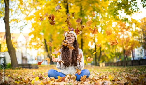 Obraz na plátne  Happy young woman throwing autumn leaves and smiling on colorful nature city bac