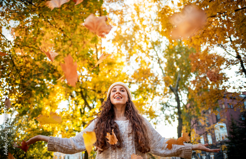 Fotografia, Obraz  Happy young woman throwing autumn leaves and smiling on colorful nature city bac