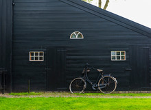Bicycle Lean On The Barn With White Window And Black Wooden Wall