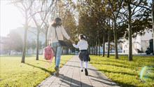 Young Woman And Little Girl In School Uniform Are Holding Hands And Running Along The Trees In The Park At Sunny Autumn Weather. Family Late For School Concept, Back View.