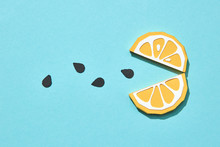 Composition Of Handcraft Paper Pieces Orange In Shaped Face Eating Seeds On A Blue Background With Copy Space. Pack-man Game Concept. Flat Lay