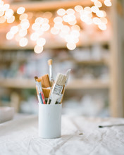 A Glass With Brushes For Painting Is On The Table
