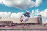 Male athlete, standing on one arm jump, summer city, hip hop style, break dancer. Cloud building background. Active youth lifestyle, modern fashionable, street dancer. Fitness t-shirt glasses jeans.