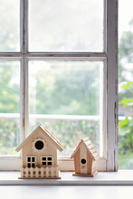 Two Wooden Bird Houses On Sunny Window Sill
