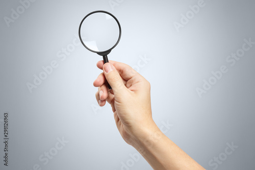 Photo Hand holding a magnifying glass on gray background