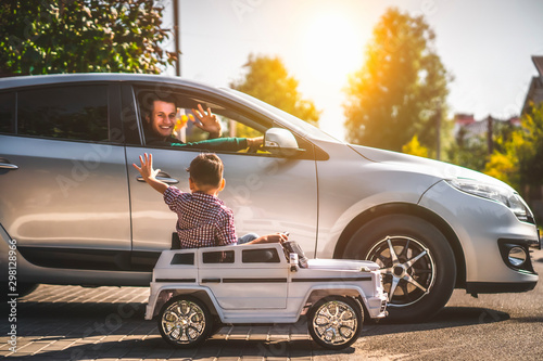 Fototapeta The father and his little son driving their cars obraz