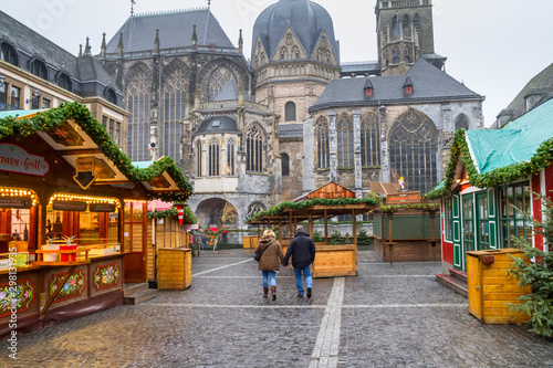 Wall Murals Northern Europe Cityscape - view of the Christmas Market with passing pair on the background the Aachen Cathedral, North Rhine-Westphalia, Germany