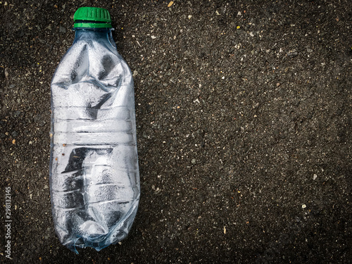 Fotografie, Obraz  Enviroment pollution, isolated plastic bottle on the street, recycle plastic and