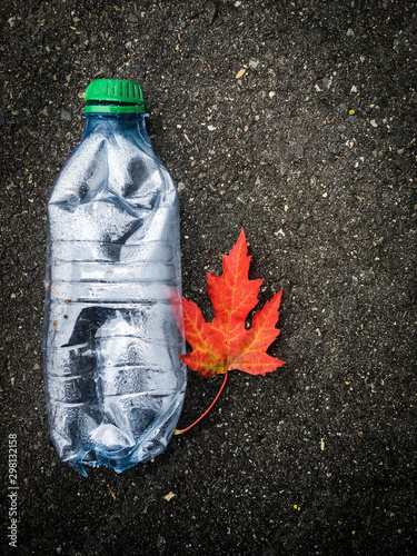 Fototapeta  Enviroment pollution, isolated plastic bottle on the street, recycle plastic and