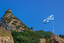 Greece Flag Waving In The Blue Sky With Green Fields At Mountain Peak Background. Nature Theme.