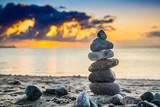 Fototapeta Łazienka - stos kamieni  na plaży o wschodzie słońca