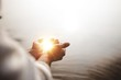 canvas print picture - Beautiful shot of Jesus Christ holding hope and light in his palms with a blurred background