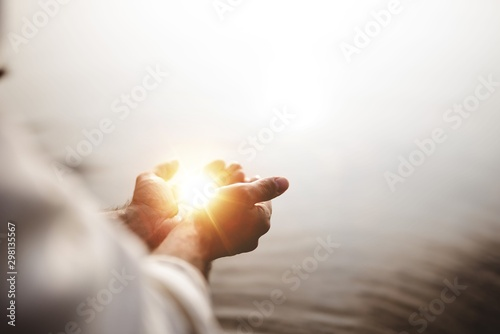 Leinwand Poster Beautiful shot of Jesus Christ holding hope and light in his palms with a blurre
