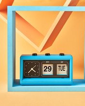 Vintage Blue Flip Clock On Wooden Square Shelf On An Yellow Background With Copy Space.