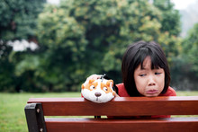 Asian Little Girl Mischievous With Dog Doll, On Park Bench