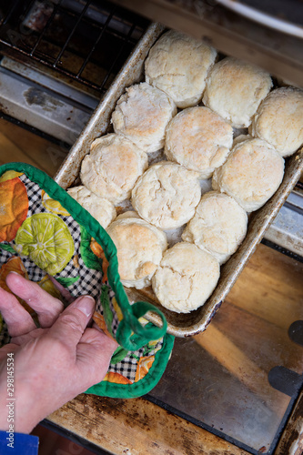 Taking homemade buttermilk biscuits in the oven