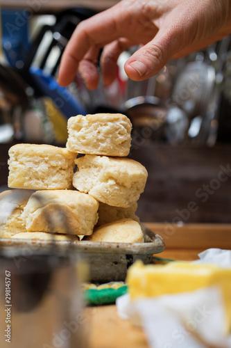 Hand grabbing a homemade buttermilk biscuits
