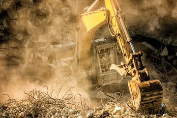 Heavy machinery surrounded with dust cloud taking down an old building