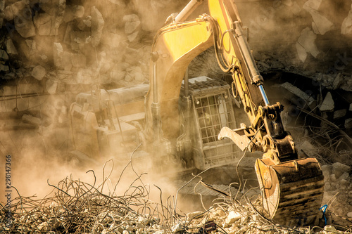 Cuadros en Lienzo  Heavy machinery surrounded with dust  cloud taking down an old building
