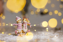 Decorative Figurines Of A Christmas Theme. Figurine Of Cute Hugging Cats Dressed In A Knitted Sweater, Scarf And Hat. Christmas Tree Decoration. Festive Decor, Warm Bokeh Lights.