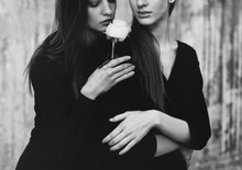 Black And White Shot Of Two Sensual Young Women Smelling White Rose