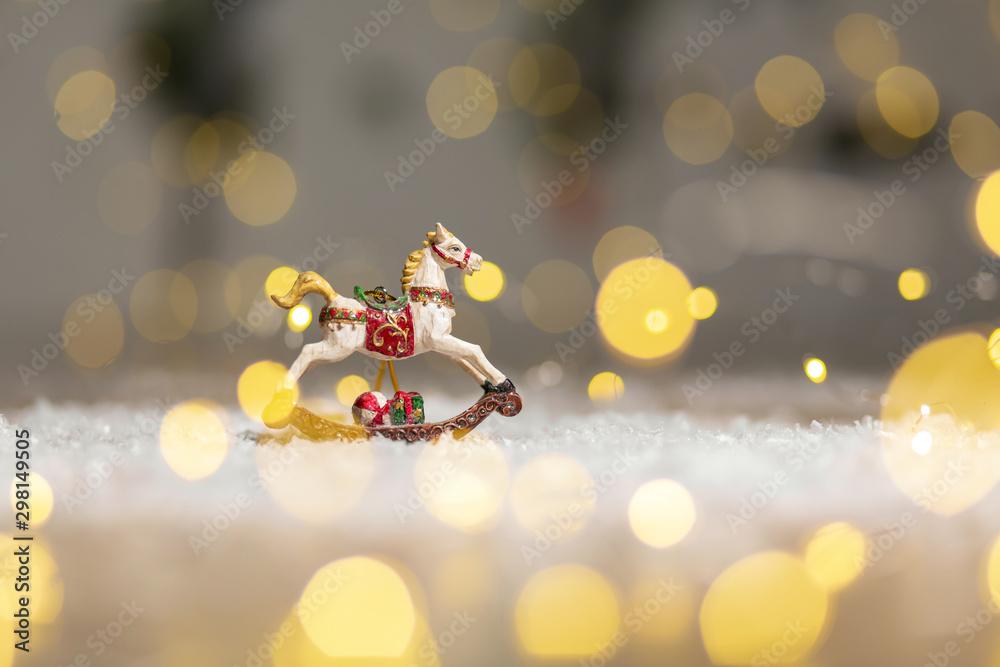 Fototapety, obrazy: Decorative figurines of a Christmas theme. Figurine of a rocking horse. Decoration for a Christmas tree. Festive decor, warm bokeh lights.