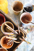 Cups Of Paint And Paint Brushes