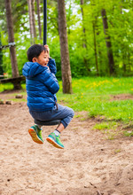 Kid Swing On Rope Happily In Playground