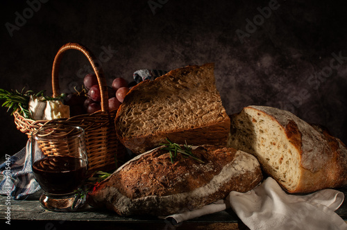 Photo  Still life bread in basket and bottle of wine. on a wooden basis