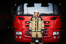 Portrait Of Female Firefighter Standing In Front Of Fire Engine At Fire Station