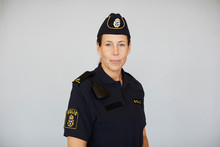 Portrait Of Policewoman In Uniform Standing Against White Background