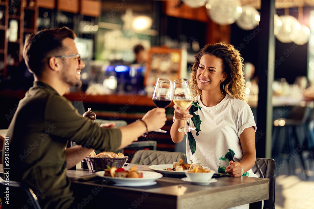 Fototapety, obrazy: Happy couple toasting with wine during lunch in a restaurant.