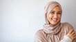 Portrait of islamic woman smiling. Pretty muslim girl. Beautiful asian muslimah woman model posing on grey wall studio. Portrait Of Arab Beauty.
