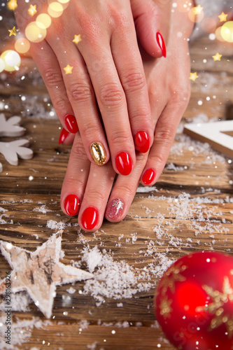 Woman with beautiful christmas red nails on vintage wooden table, top-down view Fototapeta